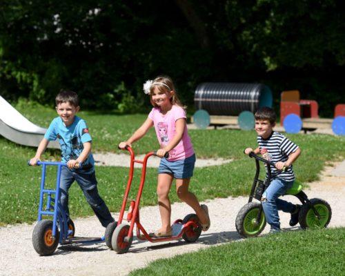 Spielende Kinder auf Tretrollern
