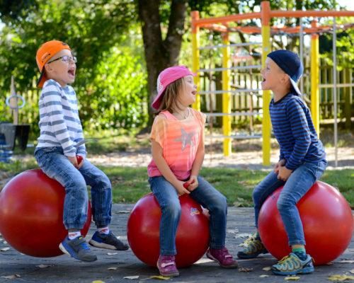 Drei spielende Kinder auf Hüpfbällen