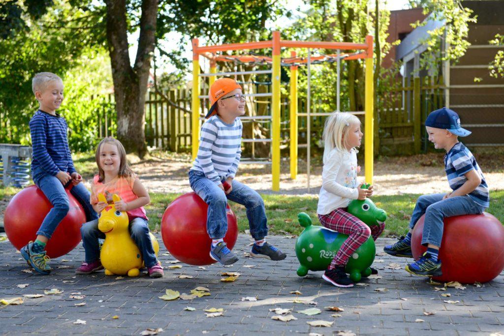 Spielende Kinder auf Hüpfbällen