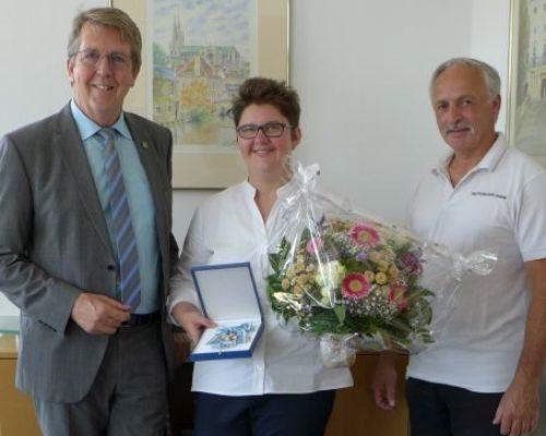 Bürgermeister Klaus Ritter und Vorsitzender des 1. CKKS Traunreut e. V., Richard Schalch, gratulieren Andreea Nowak